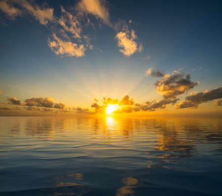 Photo pour Dramatic sunrise or sunset reflected into the calm waters of an artificial ocean to represent peace or heaven - image libre de droit