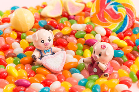 Photo for A pair of piggy dolls with candy background - Royalty Free Image