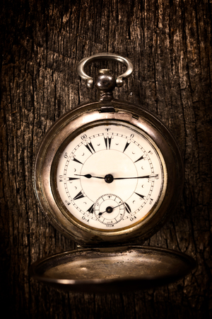 Old pocket watch on the wooden background.Selective focus in the middle of watch