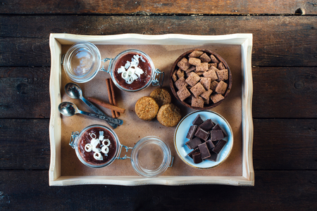 Panna cotta,chocoloate,pillows and cookies in the wooden tray from above,selective focus