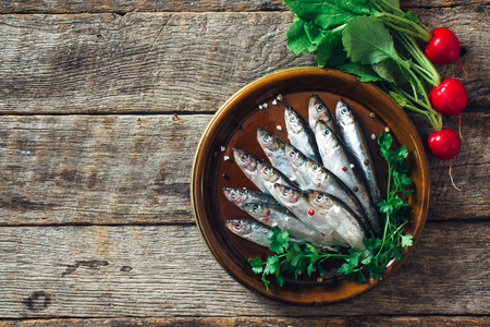 Raw smelt fishes on wooden background with blank space