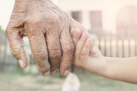Photo pour Little child holding her grandparent for hand,selective focus - image libre de droit