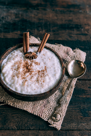 Creamy rice pudding with cinnamon in bowl on wooden background,selective focus
