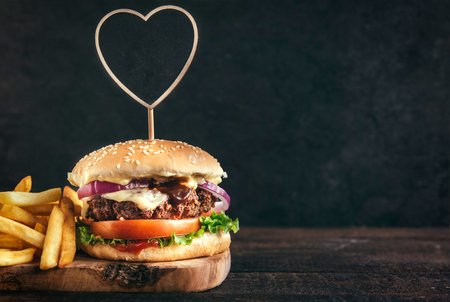 Photo pour Juicy beef burger and french fries on wooden board with blank space,selective focus - image libre de droit