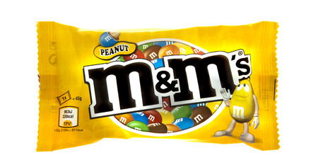 SWINDON, UK - MARCH 9, 2014: Packet of Peanut M&M's milk chocolate made by Mars Inc. isolated on white background