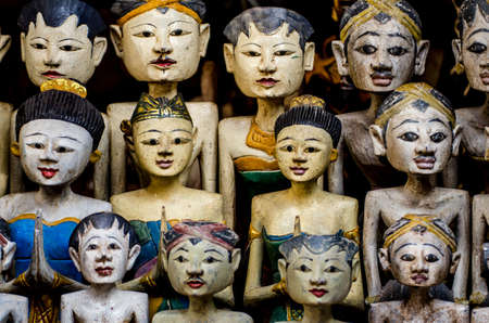 faces of asian wooden dolls in a market