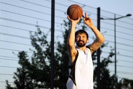 The smiling playing basketball player is throwing the basketball ball outdoor.