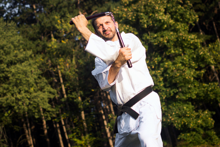 The master of martial arts in white kimono is practicing with nunchaku outdoors in nature.
