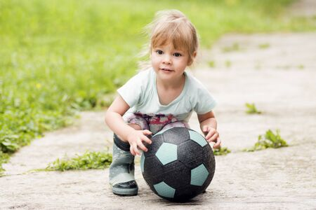 Foto de The cute little girl is playing with soccer ball on the street. - Imagen libre de derechos