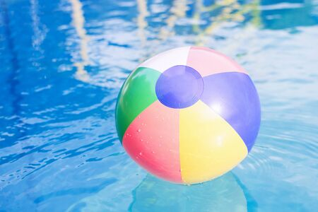 Foto de The colorful beach ball is on the water in swimming pool at summer. - Imagen libre de derechos