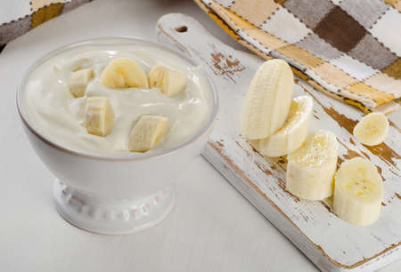 Yogurt with banana  in a white bowl   on white wooden table.