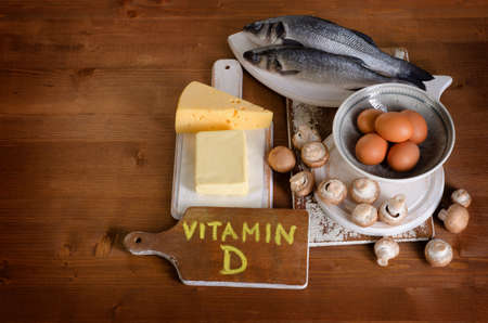 Foods containing vitamin D on wooden background. View from above