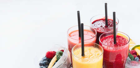 Photo pour Htalthy fresh fruit and vegetable smoothies with assorted ingredients served in packs. Image with copy space - image libre de droit