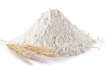 Heap of wheat flour and wheat ears on isolated white