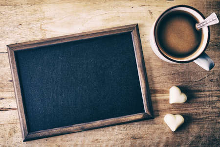 Photo pour Blank blackboard with candy hearts and cup of coffee on wooden background - image libre de droit