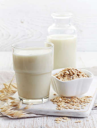 Glass of oat milk on white wooden background