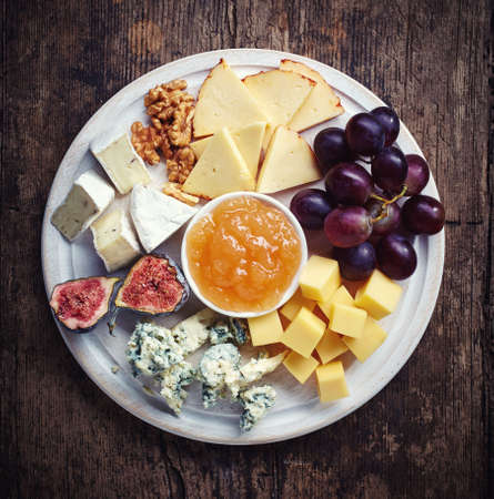 Photo pour Cheese plate served with grapes, jam, figs and nuts on a wooden background - image libre de droit