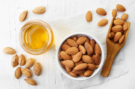 Almond oil and bowl of almonds on white wooden background. Top view
