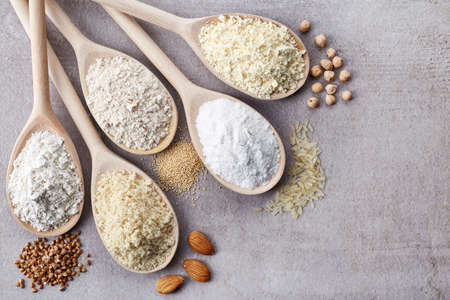 Photo pour Wooden spoons of various gluten free flour (almond flour, amaranth seeds flour, buckwheat flour, rice flour, chick peas flour) from top view - image libre de droit