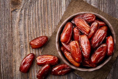 Photo for Bowl of dried dates on wooden background from top view - Royalty Free Image