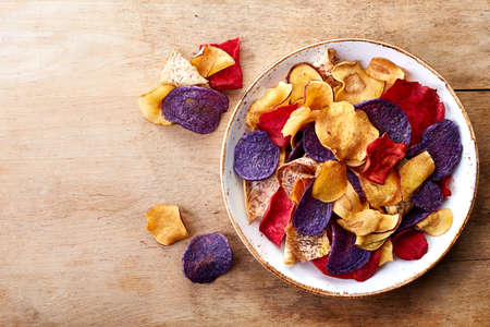 Bowl of healthy colorful vegetable chips on wooden background from top view