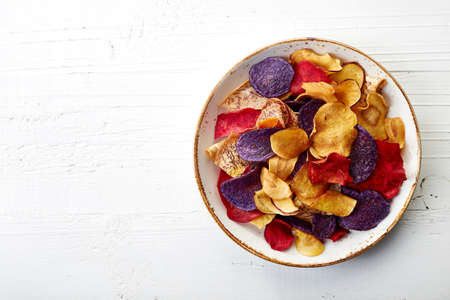 Bowl of healthy colorful vegetable chips on white wooden background from top viewの写真素材