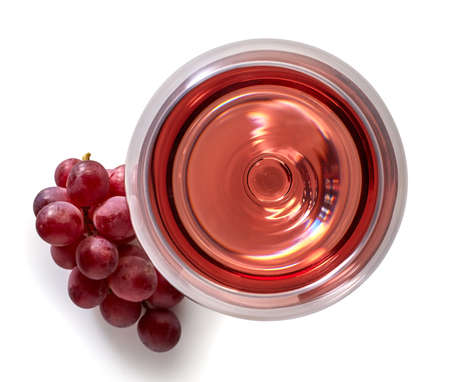 Foto de Glass of rose wine and grapes isolated on white background from top view - Imagen libre de derechos