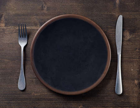 Photo pour Black empty plate and cutlery on dark wooden background, top view - image libre de droit