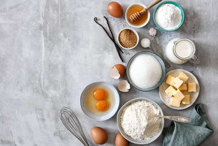 Photo pour Baking ingredients: flour, eggs, sugar, butter, milk and spices on gray marble background. Top view. Space for text - image libre de droit