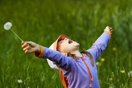 a very happy girl with dandelion arms outstretched against a background of green grass