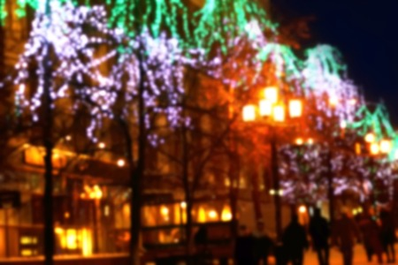 blurred vintage background. trees decorated with lights on the street. Christmas city outdoors