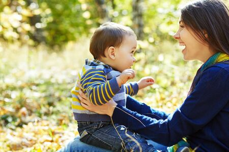 Photo for walking and playing young mother with her baby outdoors. Mom and son in an autumn park. - Royalty Free Image