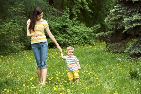 Photo for outdoor portrait of a mother with her child. Mom and son walking in a summer park on the grass with yellow dandelions. - Royalty Free Image