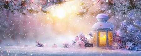 Foto de Christmas Lantern On Snow With Fir Branch in the Sunlight. Winter Decoration Background - Imagen libre de derechos