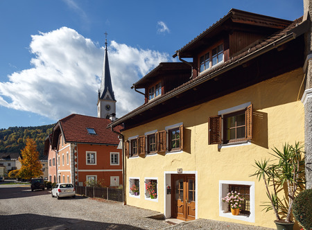 GMUEND IN KAERNTEN / AUSTRIA - OCTOBER 10, 2017. Beautiful paved street with old residential houses and gothic parish church. Gmuend in Kaernten, district of Spittal an der Drau, federal state of Carinthia, Austria