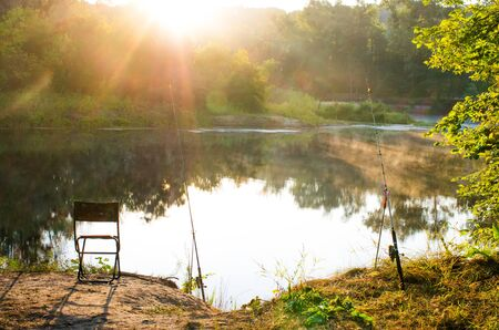 Photo pour stand fishing rod and stool by the river - image libre de droit