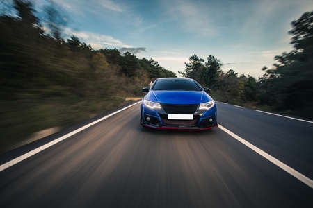 Photo for Blue sport car front view drive on the road - Royalty Free Image
