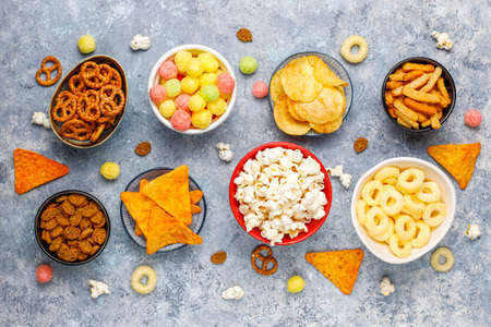 Foto de Salty snacks. Pretzels, chips, crackers,popcorn in bowls. Unhealthy products. food bad for figure, skin, heart and teeth. Assortment of fast carbohydrates food - Imagen libre de derechos