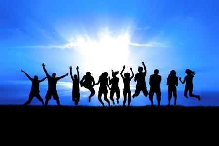 Photo pour Silhouettes of a celebratory group jump in field of grass, bright sun behind - image libre de droit