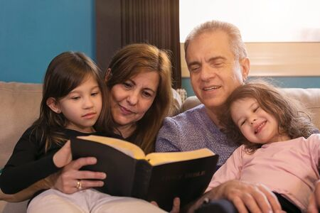 Photo for Grandparents teaching grandchildren about the Holy Bible - Royalty Free Image