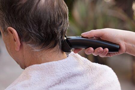 Foto für Family member cutting mans hair at home - Lizenzfreies Bild