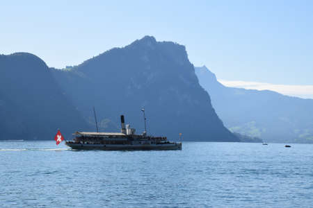 Vitznau, Switzerland 29.09.2019: A steamboat with Swiss flag on the back is crossing Lake Lucerne
