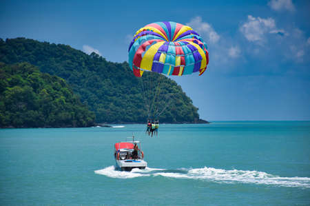 Photo for Parasailing on the waves of the azure Andaman sea under the blue sky near the shores of the sandy beautiful exotic and stunning Cenang beach in Langkawi island, in Malaysia. - Royalty Free Image