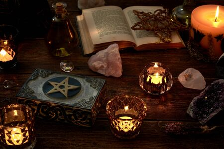 Photo for Esoteric or mystical still life with a box and a few burning candles, a pentagram next to an open book. Pendulum and precious stones on old wooden table top. - Royalty Free Image