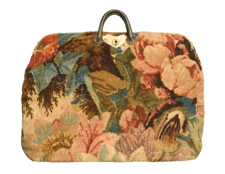 An antique carpetbag with a flower pattern isolated against a white background