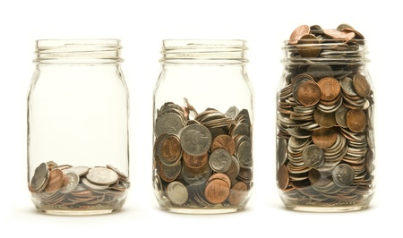 Increasing numbers of American coins in a three glass jars against a white background