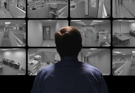 Photo pour Security guard conducting surveillance by watching several security monitors - image libre de droit