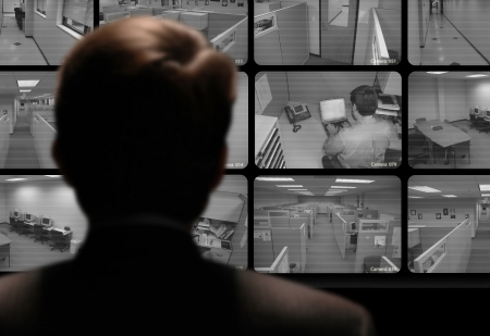 Photo pour Man watching an employee work via a closed-circuit video monitor - image libre de droit