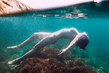Nude woman is underwater. Young woman with naked body in sea
