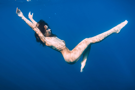 Beautiful naked woman relaxed in sea, underwater in blue ocean